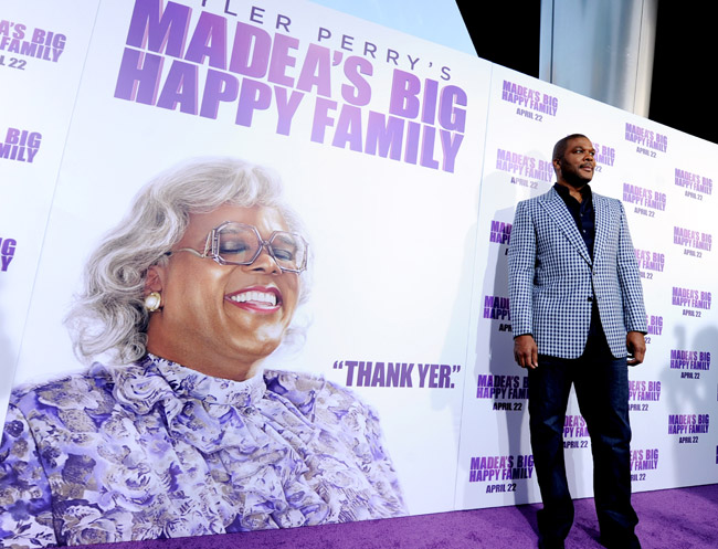 "Tyler Perry next to a giant picture of Madea ""Thank yer"""