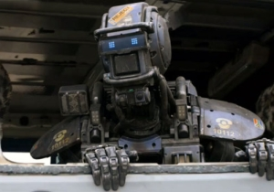 See 'Chappie' In Action And Hugh Jackman's Glorious Mullet In These New Clips