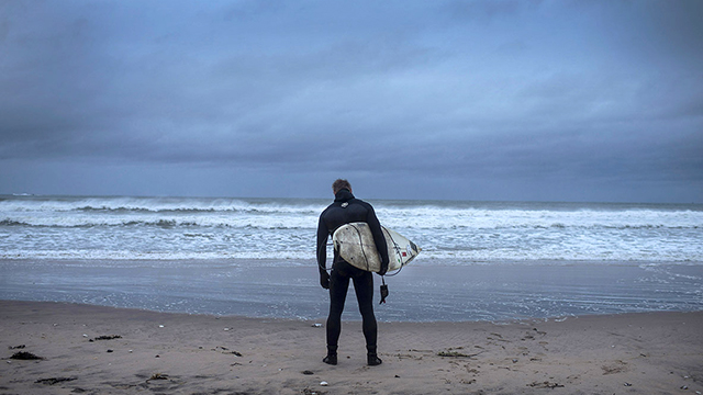 PORTRUSH, NORTHERN IRELAND - DECEMBER 6: Pro surfer Alastair Mennie watches the sea as he prepares to surf Storm Desmond on December 6, 2015 in Portrush, Northern Ireland. Storm Desmond has brought major disruption to the United Kingdom with thousands of homes left without power and severe flooding across many areas. (Photo by Charles McQuillan/Getty Images)