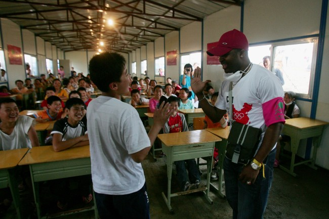 MIANZHU, SICHUAN - MAY 21: A volunteer from Nigeria teaches English in the temporary classroom at a relief center on May 21, 2008 in Deyang of Sichuan Province, China. China fight against time to deliver relief supplies to survivors amidst concerns of possible disease outbreaks. More than 40,000 people have been confirmed killed and about five million people were made homeless by the May 12 earthquake measuring 8.0 on the Richter scale, the worst in 58 years to hit China. (Photo by Feng Li/Getty Images)