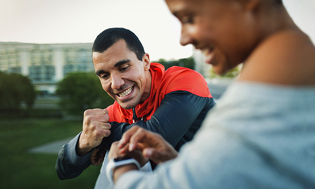 Man celebrating victory while woman checking time on smart watch