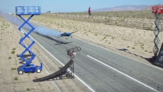 This Crazy Motorcycle Jumping A Speeding Plane Stunt Is Made Crazier With A Tight Rope Walker